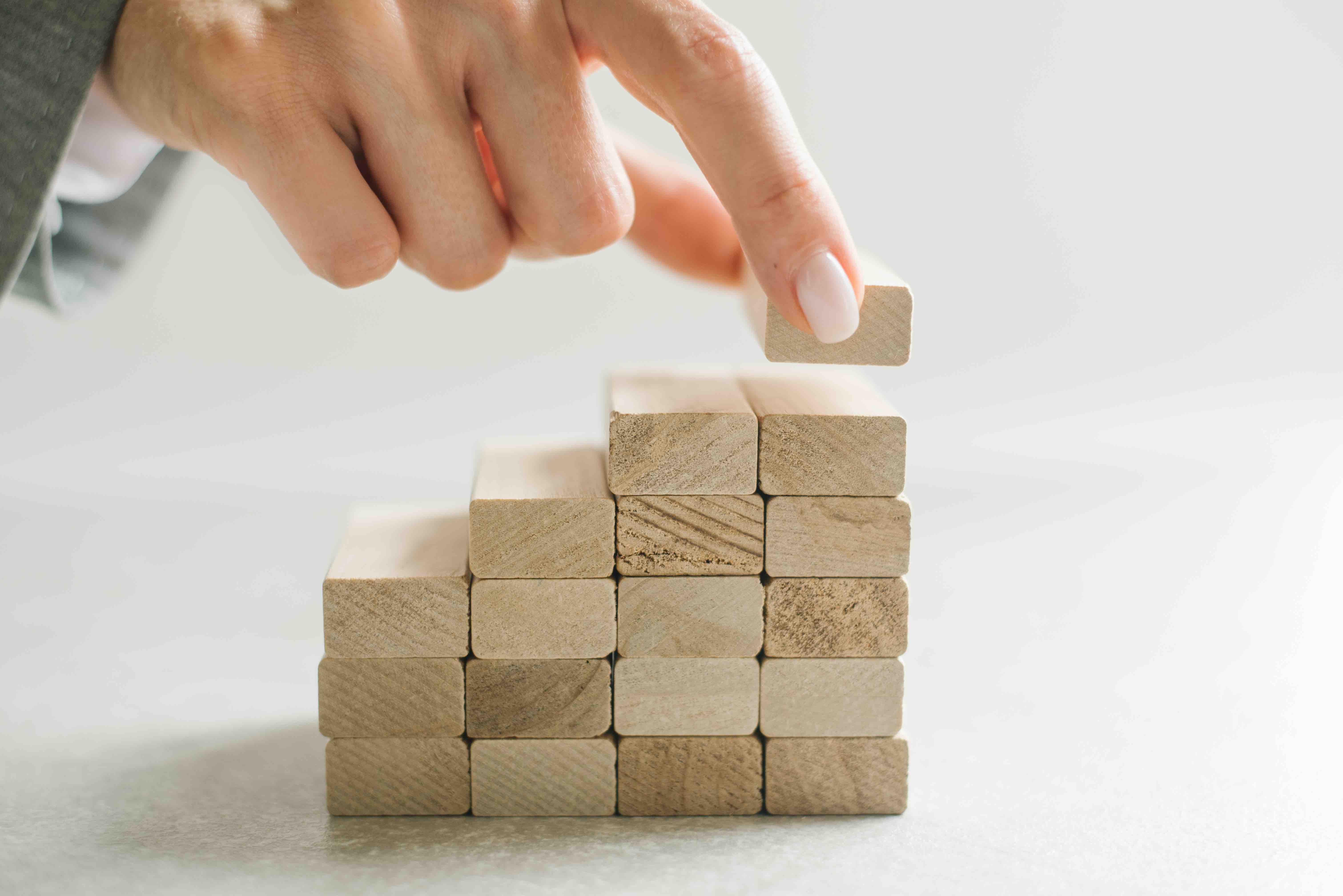 bigstock-Women-Hand-Putting-A-Wooden-Bl-375860800