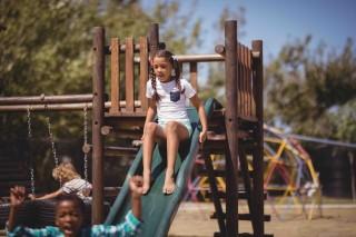 bigstock-Girl-playing-on-slide-at-schoo-188749567